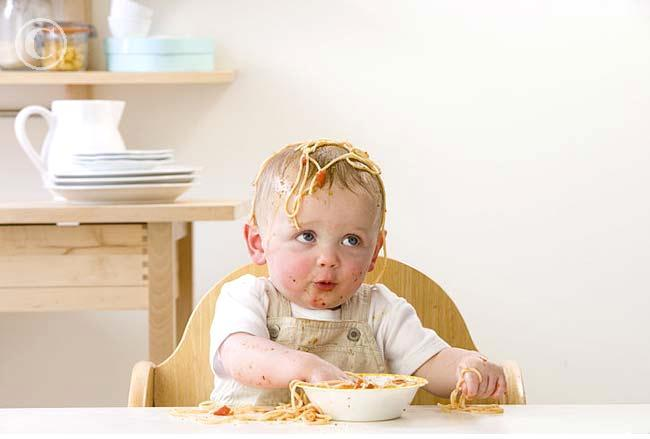 messy_baby_boy_in_high_chair_eating_spaghetti_24054