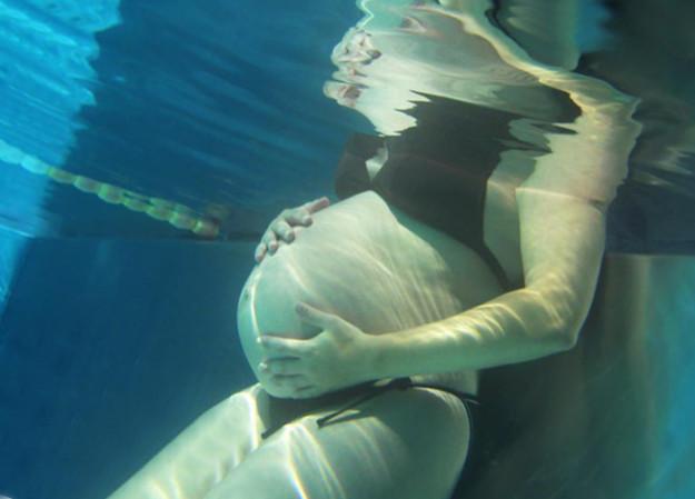 Babybauch einer schwangeren Frau unter Wasser im Pool