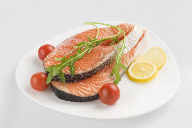 Raw salmon steak with herbs and tomatoes