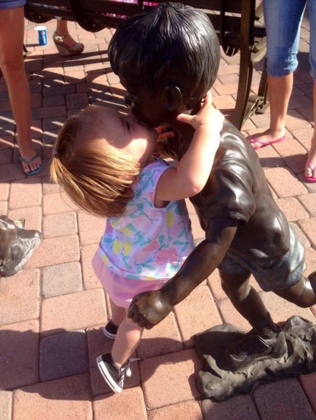 девочка фотографируется с памятником