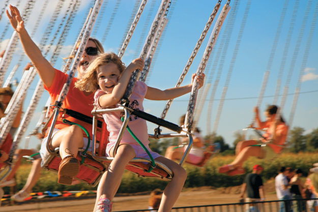 A mother and daughter having fun on amusement park swings.
