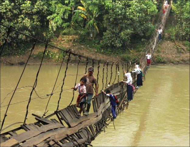 В Индонезии дети по пути в школу переходят через реку по сломанному мосту