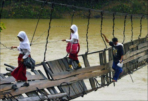 В Индонезии дети по пути в школу переходят через реку по сломанному мосту2