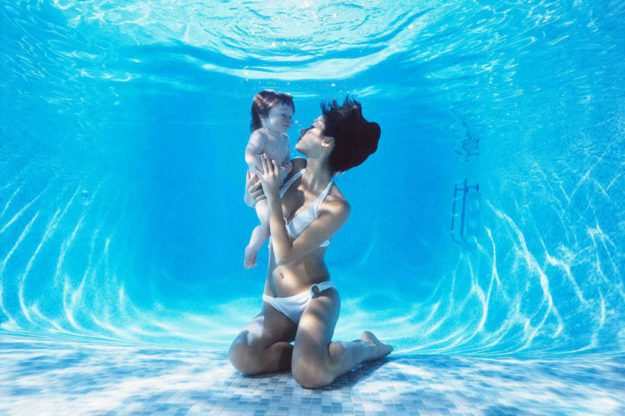 Mother and baby submerged below the surface in a clear blue swimming pool. Relaxed and happy underwater the water the child learns to swim with her parents