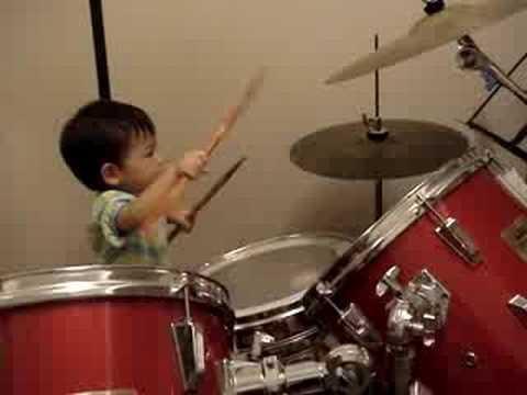 Двухлетний мальчик круто играет на барабанах